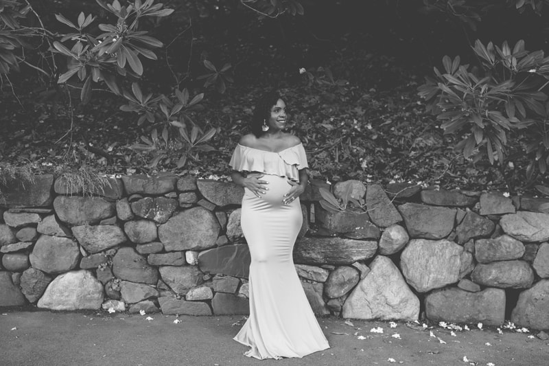 Maternity Photography, black and white of woman leaning against a stone wall