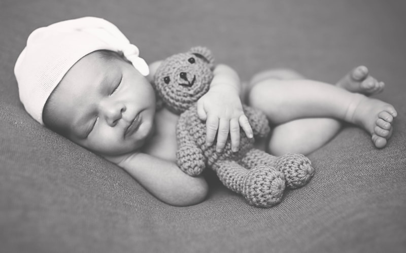 Newborn Photography, black and white of baby holding bear