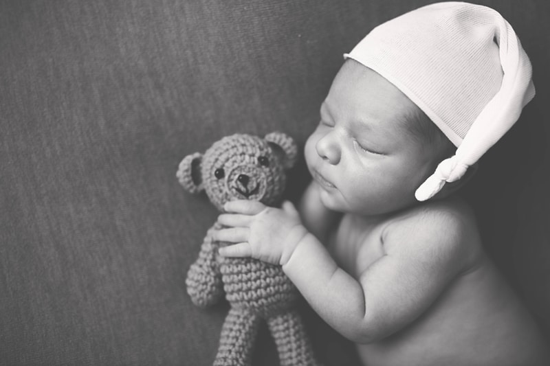 Newborn Photography, black and white of baby with little bear