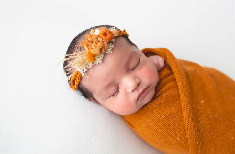 Newborn Photography, baby wrapped in orange blanket