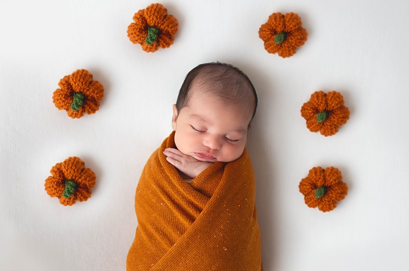 Newborn Photography, baby wrapped in orange blanket with crocheted pumpkins