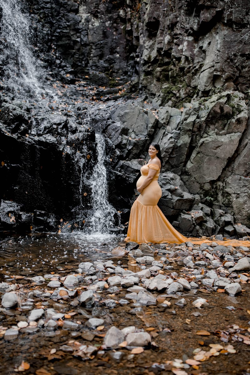 Maternity Photography, woman in yellow next to a waterfall