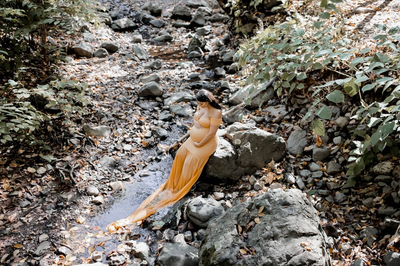 Maternity Photography, wide angle shot of woman with yellow dress next to a creek