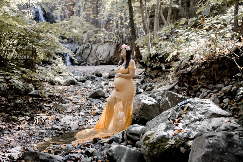 Maternity Photography, woman standing next to a creek in yellow dress