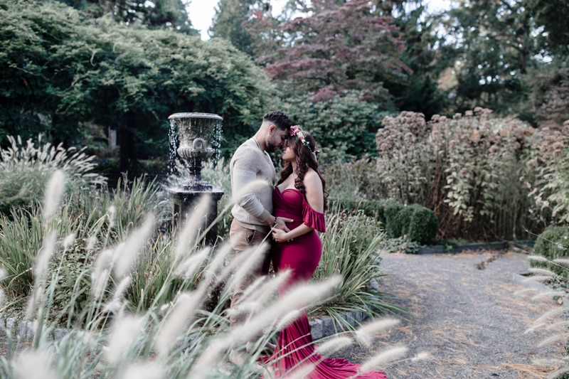 Maternity Photography, man and woman standing next to a fountain
