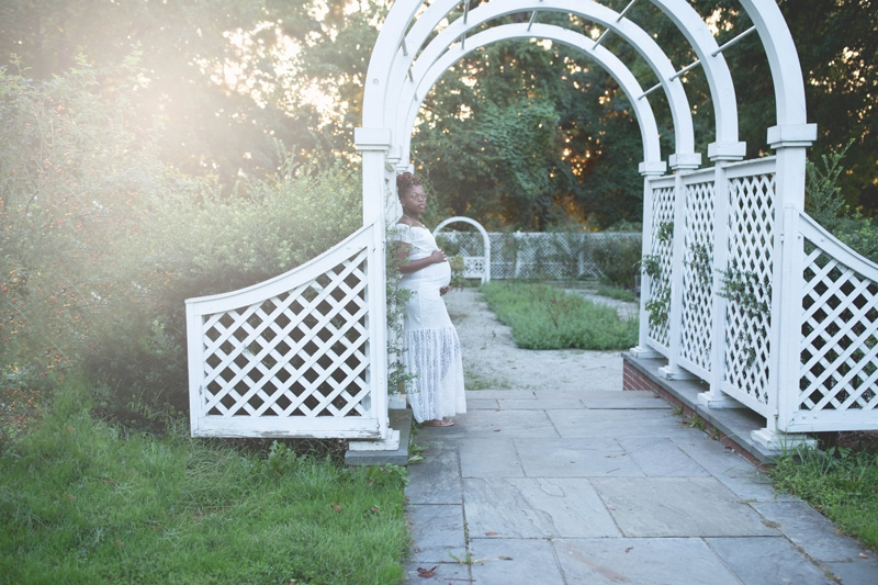 Maternity Photography, pregnant woman leaning against an white arch
