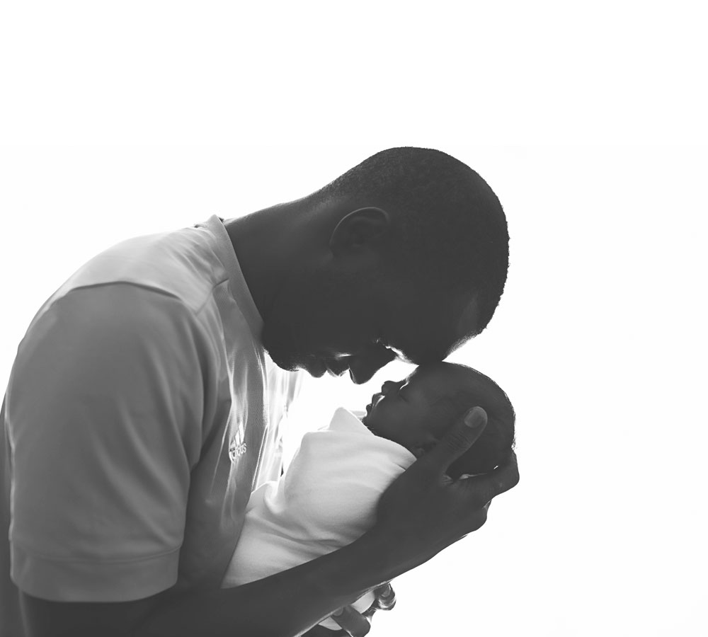 Newborn Photography, man holding a baby against a white background